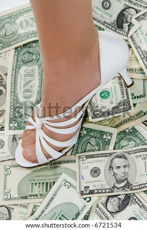 Woman stands on a pile of cash to insinuate that it is hers. - stock photo