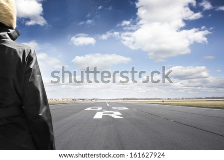 Woman stands on airport runway looking to the horizon
