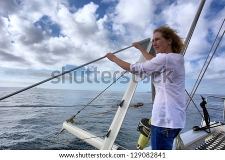 Woman stands on deck - view against dramatic skies. Shot near Cape Town, Western Cape, South Africa. - stock photo