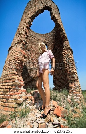 Woman staying against abandoned ruins at sunny summer day - stock photo