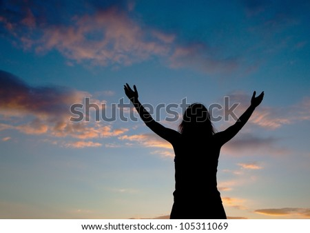 Woman staying with raised hands at the sunset time - stock photo