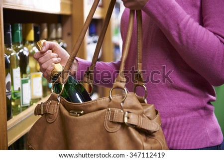 Woman Stealing Bottle Of Wine From Supermarket - stock photo