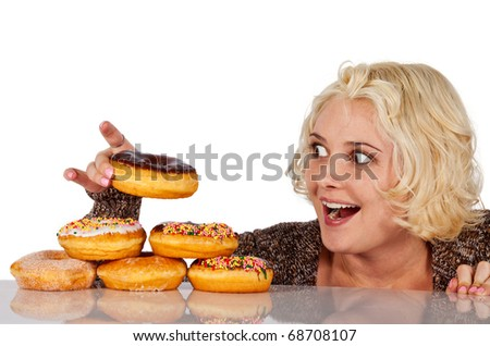 Woman steals a donut off a pile of donuts - stock photo