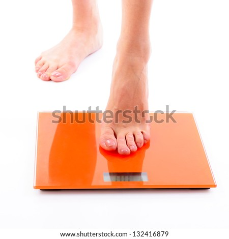 Woman steps on scales. Over white background - stock photo
