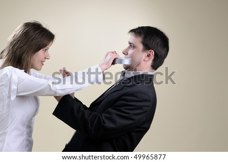 woman sticking her colleague mouth - stock photo