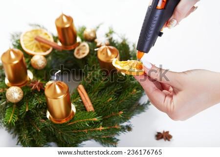 Woman sticking orange hot gun on Christmas wreath on a white table - stock photo