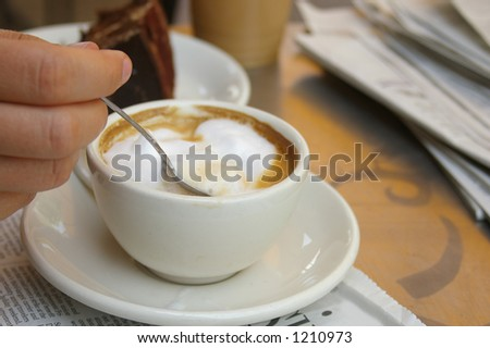 woman stirring a cappuccino - stock photo