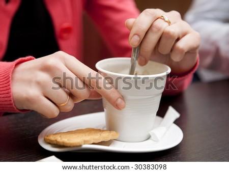 Woman stirring coffee, close-up, shallow DOF - stock photo