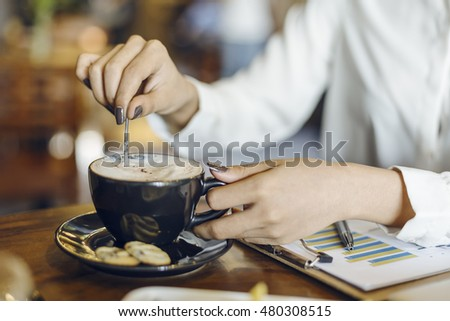 woman stirring coffee in a cup with cookies