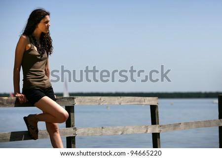 Woman stood alone on jetty - stock photo