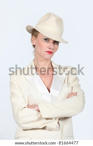 Woman stood arms folded wearing  a cream jacket and hat - stock photo