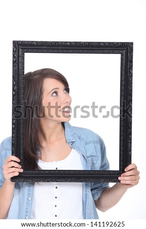 Woman stood holding empty picture frame - stock photo