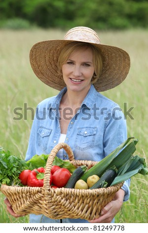 Woman stood in field carrying basket of vegetables - stock photo