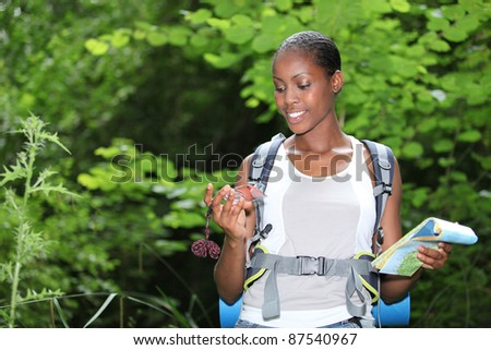 Woman stood outdoors holding compass and map - stock photo