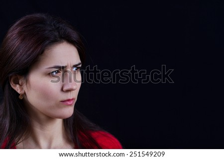 Woman stressed with upset look,looking to her left to her left .Close-up of young woman on black background. - stock photo