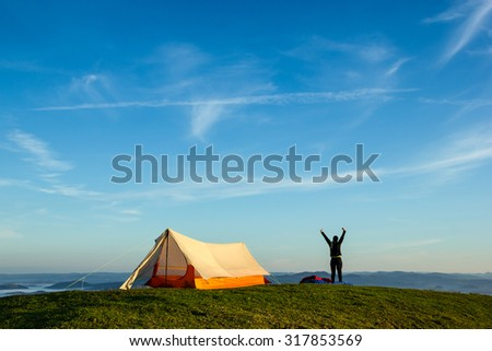 Woman Stretching After a Night on the Tent on the top of a Mountain - stock photo
