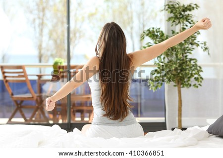 Woman stretching arms and waking up sitting on the bed in an hotel or home bedroom looking the sea outdoors through the window - stock photo
