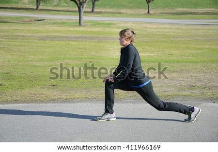 woman stretching before exercise running outside  - stock photo