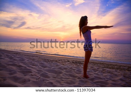 woman stretching both arms relaxing on the beautiful sunset beach