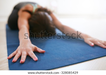 Woman stretching forward, performing a yoga pose on exercise mat. Fitness female performing balasana yoga at gym, focus on hands. - stock photo