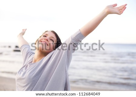 Woman stretching her arms to enjoy the fresh air of the sea - stock photo
