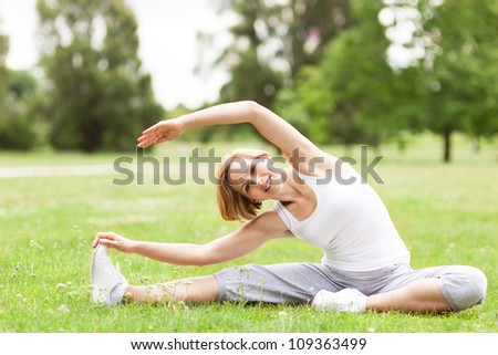 Woman stretching in a park - stock photo