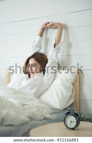 Woman stretching in bed after wake up,vintage tone,flare light
