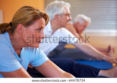 Woman stretching in gym in a fitness class - stock photo