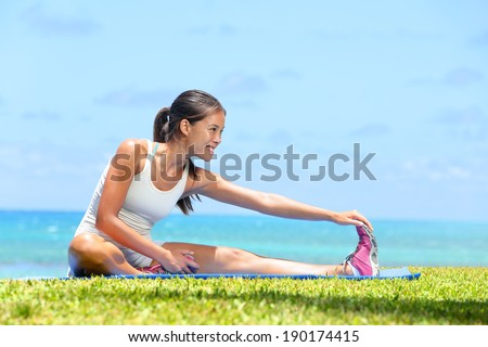 Woman stretching legs exercise training fitness outside by the ocean sea. Beautiful fit female fitness girl model sitting on grass doing stretch exercising after workout. Mixed race Asian female model - stock photo