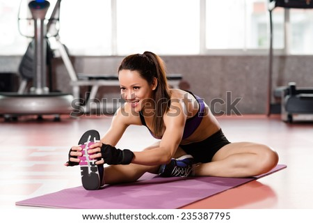 Woman stretching legs in sports club - stock photo