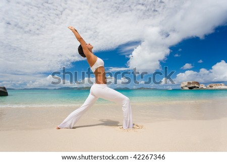 woman stretching on tropical beach in white yoga outfit with clouds and turquoise water exercising