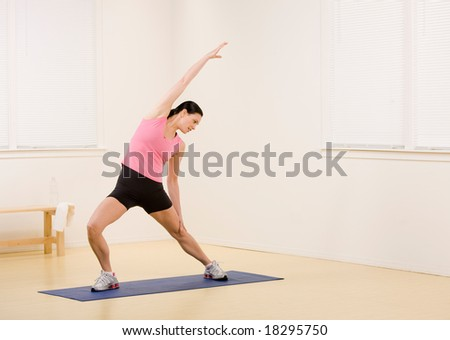 Woman stretching on yoga mat in fitness studio