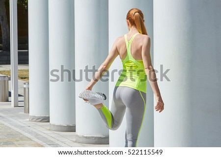Woman stretching outdoor bending leg in the city, sunny day