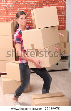 Woman struggling to carry boxes - stock photo