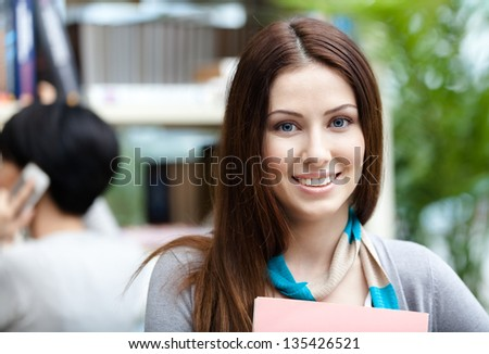 Woman student at the library against bookshelves and her friend. Study - stock photo