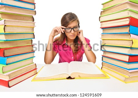 Woman student sitting at the desk surrounded with piles of books. Isolated - stock photo