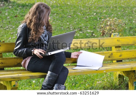 woman studying with a laptop and papers on bench in park - stock photo