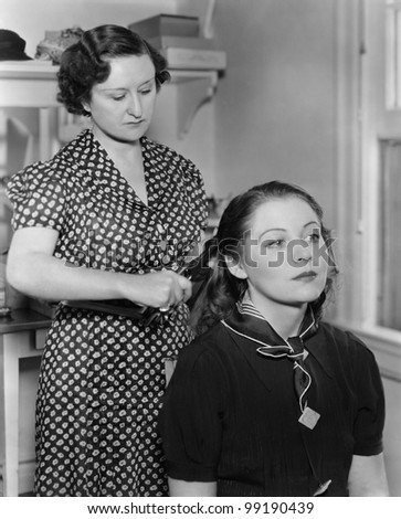 Woman styling another womans hair - stock photo