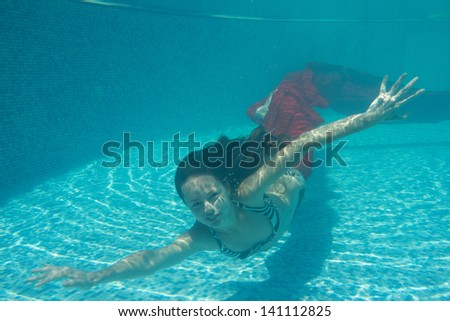 woman submerged with red fabric under water