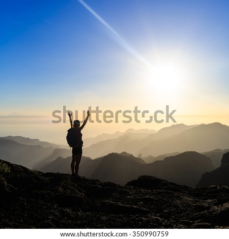 Woman successful hiking climbing silhouette in mountains, motivation and inspiration in beautiful sunset and ocean. Female hiker with arms up outstretched on mountain top, inspirational landscape.