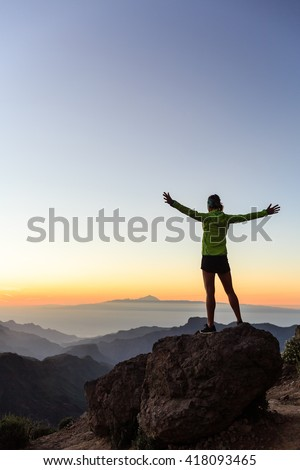 Woman successful hiking climbing silhouette in mountains, motivation and inspiration in beautiful sunset and ocean. Female hiker with arms up outstretched on mountain top looking at night landscape. - stock photo