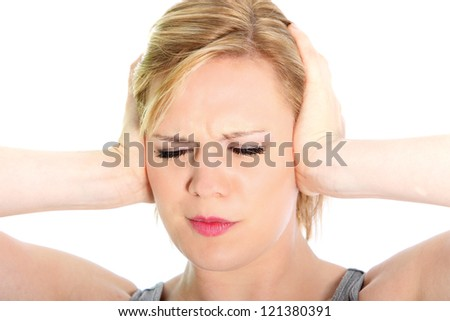 Woman suffering from a headache grimacing and holding her hands to her ears to relieve the throbbing, closeup studio head portrait on white - stock photo