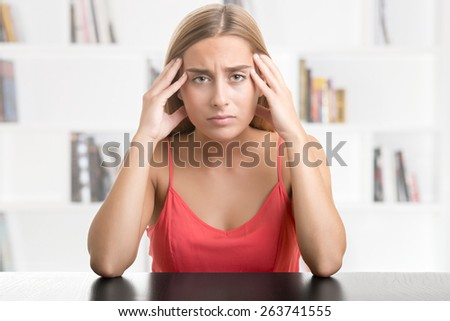 Woman suffering from an headache, holding her hand to the head, in a library - stock photo