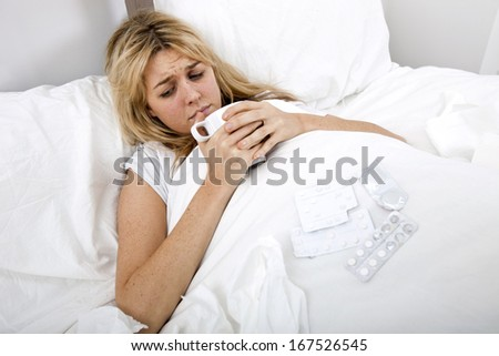Woman suffering from cold having coffee in bed - stock photo