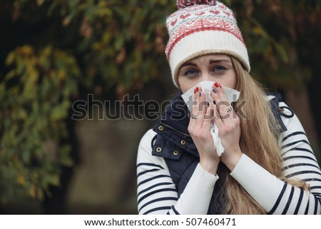 Woman Suffering From Cold outdoor with Tissue
