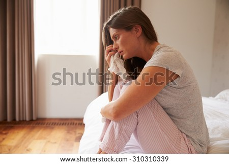Woman Suffering From Cold Sitting On Bed With Tissue - stock photo
