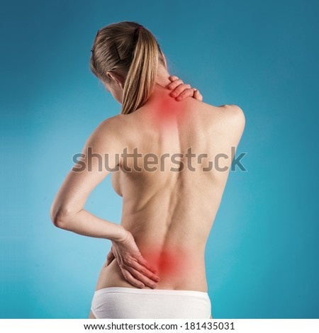 Woman suffering from lumbago or back pain. Young Caucasian female with osteoporosis indicated by red spots.  - stock photo