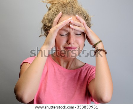 Woman suffering from stress or a headache grimacing in pain as she holds her head