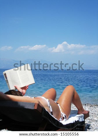 woman sunbathing and reading at the sea - stock photo