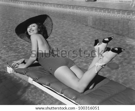 Woman sunbathing at pool - stock photo